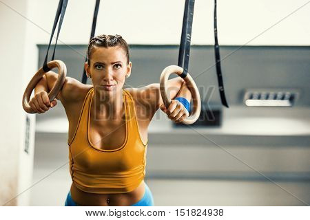 Young fit woman pulling up on gymnastic rings.