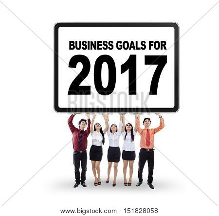 Image of businessteam standing in the studio while lifting a billboard with business goals for 2017 isolated on white background