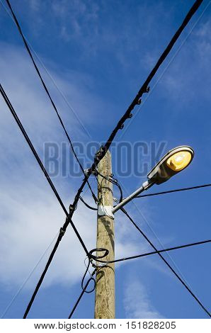 view of an electric pole with street light over a blue sky