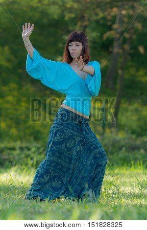 Woman doing yoga exercise, trees in background