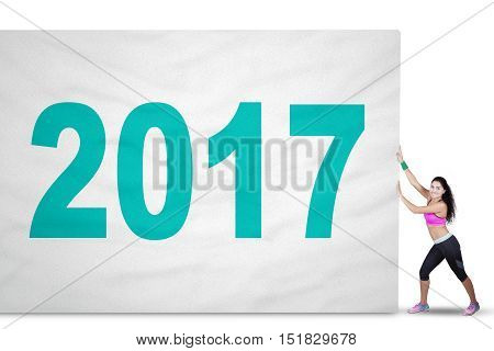 Concept of Happy New Year 2017. Picture of a fit woman wearing sportswear and pulling a big flag with number 2017