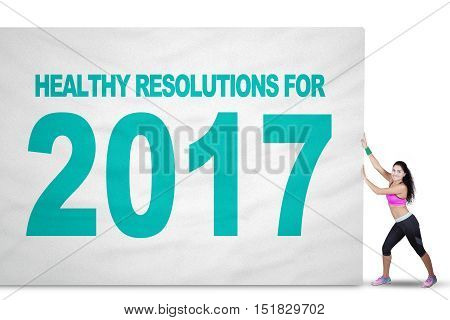 Image of a fit Indian woman pulling a big flag with text of healthy resolution and number 2017