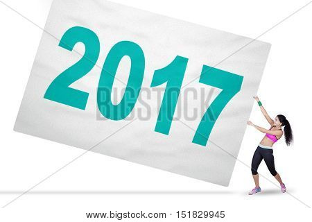 Concept of Happy New Year 2017. Healthy woman wearing sportswear and pulling a big banner with number 2017