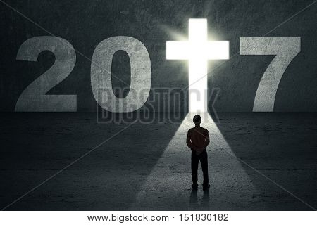 New Year 2017 is coming concept. Silhouette of a male entrepreneur looking at a doorway shaped a cross symbol with number 2017