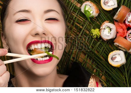 beautiful smiling young Korean girl eating sushi rolls