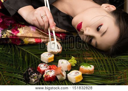 beautiful elegant Korean girl lying on table and eating rolls