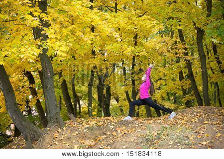 Sporty beautiful smiling young woman practicing yoga, standing in Warrior I posture, Virabhadrasana One pose, working out outdoors in autumn park wearing bright sportswear. Full length, side view