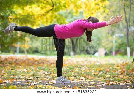 Sporty beautiful young woman practicing yoga, standing in Warrior III posture, Virabhadrasana Three pose, working out outdoor on autumn day wearing bright sportswear sweatshirt. Full length, side view