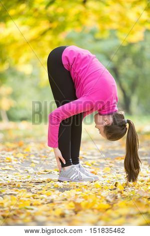Sporty beautiful young woman practicing yoga, doing uttanasana intense stretch pose, Standing forward bend or head to knees pose , working out outdoors in autumn park. Full length, vertical image