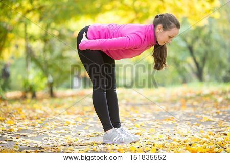 Full length portrait of sporty beautiful young woman practicing yoga, doing ardha uttanasana intense stretch pose, Standing half forward bend or head to knees pose , working out outdoors in autumn