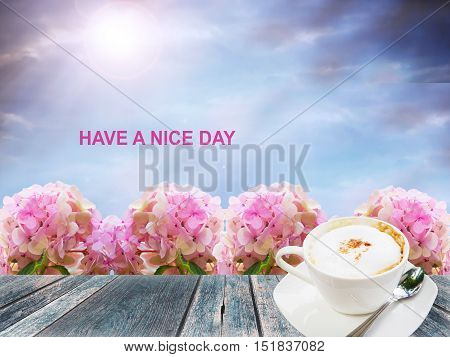 """A cup of coffee with flower and """"Have a nice day"""" wording"""