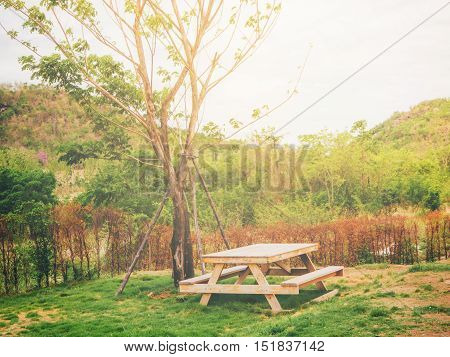 Wood table in the garden with warm filter