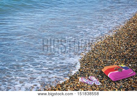 On the pebbly beach at the water's edge are beach sandals and a towel.