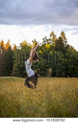 Joyful young woman leaping in a meadow under a cloudy sky throwing her arms into the air side view.
