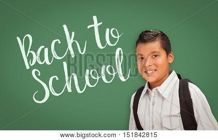 Cute Hispanic Boy Wearing A Backpack In Front of  Chalk Board with Back To School Written On it.