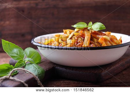 ragout of zucchini and tomato with garlic and basil in a white plate selective focus