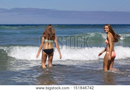 Teenage Girls in Bikinis Going into the ocean at the beach.  One is looking back smiling.  Shot in Southern California