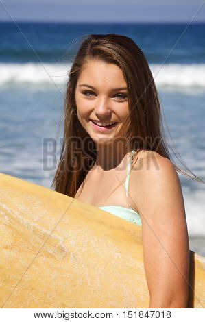 Close up of a beautiful teenage Girl with a Surfboard at the beach in Southern California