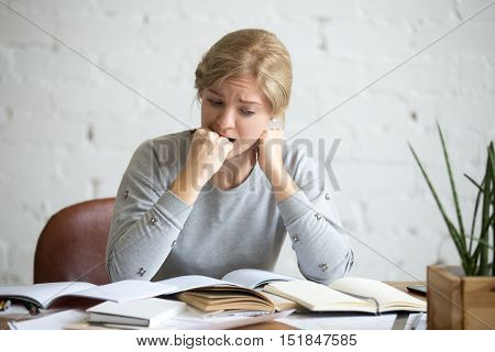 Portrait of a frustrated student girl sitting at the desk biting her fist. Education concept photo, lifestyle