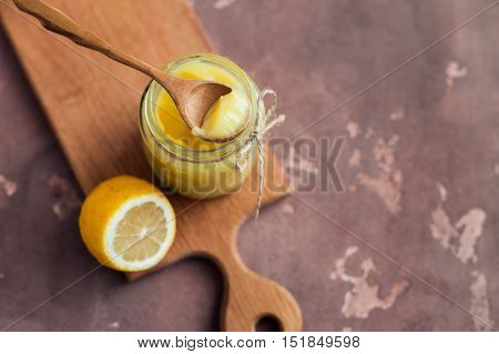 Lemon curd in glass jar with fresh lemon on concrete background.