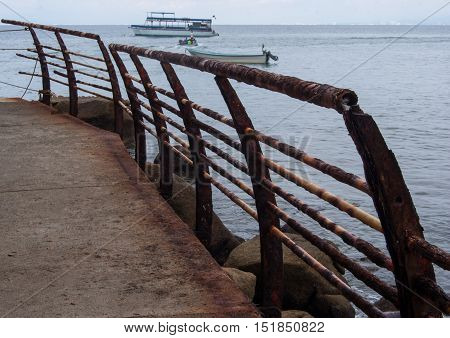 A broken down rusty railing along a seawall with ocean and boats in the background