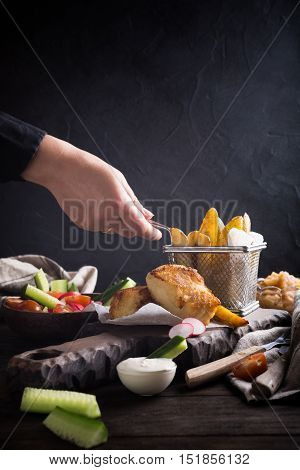 Fish and chips. Fried fish fillet with homemade baked potatoes and fresh salad on wooden cutting board with human hand.