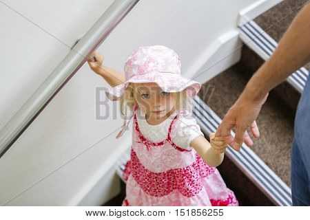 Charming little caucasian girl in pink floral dress looking up , walking downstairs