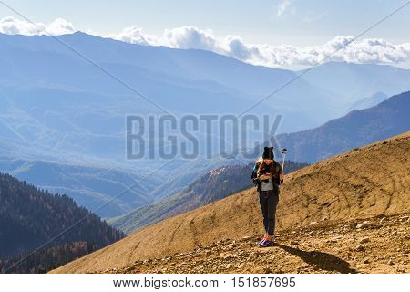 Sochi Russia - October 31 2015: Sweet young girl makes selfie with action-camera on background of autumn mountain landscape. Views of hills and peaks of Caucasus mountains. Krasnaya Polyana - Alpine ski resort. Rosa Khutor Sochi Russia