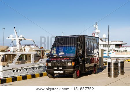 Sochi Russia - November 1 2015: Parked food truck - black truck-refrigerator Mercedes brought two barrels of beer at pier in Sochi seaport. Marine station complex Port. Krasnodarskiy kray Russia