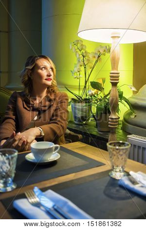Middleaged pretty woman sits with tea and looks up in cozy restaurant