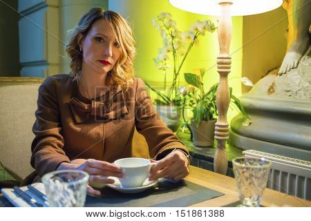 Middleaged pretty woman sits with tea and looks at camera in cozy restaurant