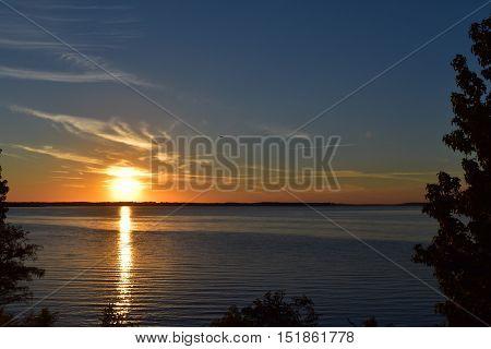 Anochecer en Lake of Pines, Texas. Reflejo del sol en las aguas calmadas con colores dorados y azules intensos