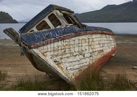 Abandoned and neglected fishing boat drawn up on the beach at Puyuhuapi along the Carretera Austral in Chilean Patagonia.