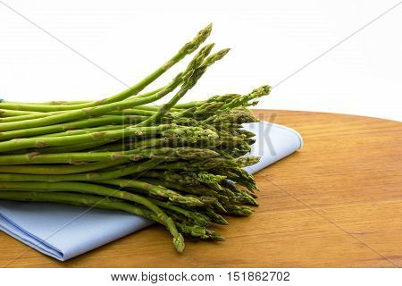 Fresh uncooked asparagus placed on pale blue napkin and wood board. Horizontal image of garden vegetable with copy space.