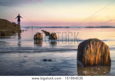 Old dock collapsed with person to the end. Sunset