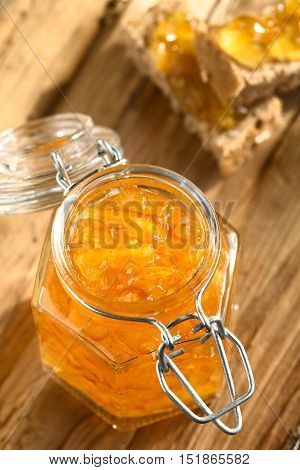 Orange jam in swing-top jar on wood with orange jam on bread in the back photographed with natural light (Selective Focus Focus on the first two orange peels on the jam)