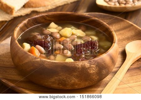 Traditional Hungarian Babgulyas (bean goulash) a soup made of pinto beans smoked meat potato carrot csipetke (homemade soup pasta) served in wooden bowl photographed with natural light (Selective Focus Focus in the middle of the soup)