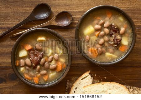 Traditional Hungarian Babgulyas (bean goulash) a soup made of pinto beans smoked meat potato carrot csipetke (homemade soup pasta) garlic onion served in rustic bowls bread and spoons on the side photographed overhead with natural light
