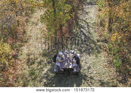 horizontal  over head image of a father and teenage son sitting at a picnic table at the end of a long hike in the woods in the fall time surrounded by a lot of autumn colors.