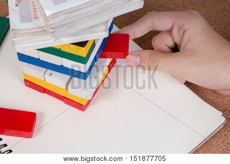 Closeup hand boy take one block on the stack toy wooden block with money on top