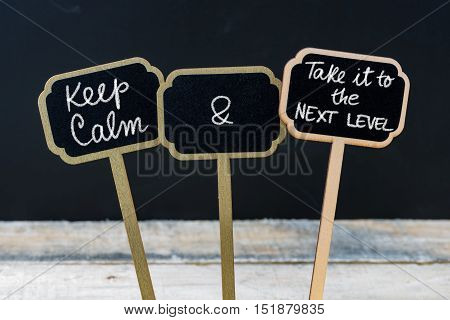 Keep Calm And Take It To The Next Level Message Written With Chalk On Mini Blackboard Labels
