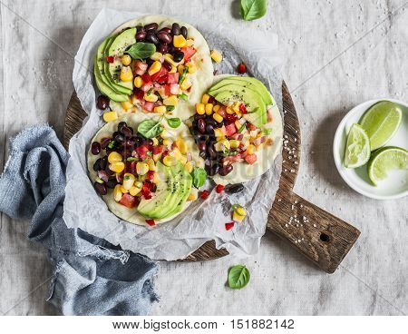 Spicy bean tostadas with corn salsa and avocado on a light background top view. Delicious vegetarian lunch or snack