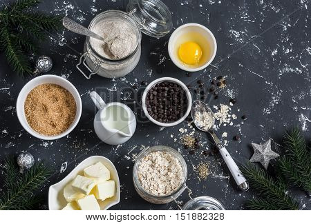 Christmas baking background. Flour sugar butter rolled oats eggs chocolate chips on a dark background. Baking ingredients