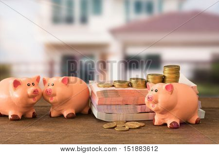 piggy bank money with house in background. concept of savings plan investment loan mortgage for house real estate residence. soft focus.