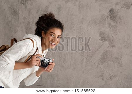 Young attractive female photographer smiling, holding camera, looking out over beige background. Copy space.