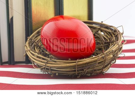 Red nest egg in front of books on American flag pattern. Still life reflects how high cost of education builds debt and affects investments.