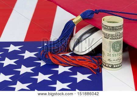 Graduation cap with tassle placed with computer mouse and dollar currency on American flag pattern. Concept symbolized is the higher salary and job opportunities of degree associated with electronics and digital knowledge.