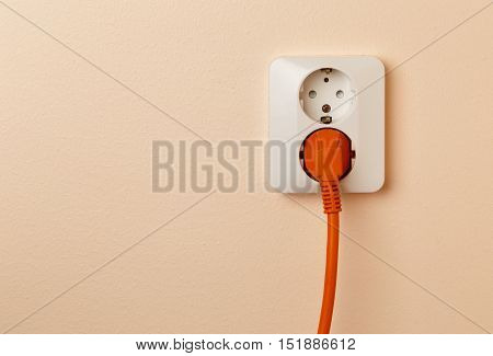One orange colored power plug with cord connected to a wall socket common in Europe.