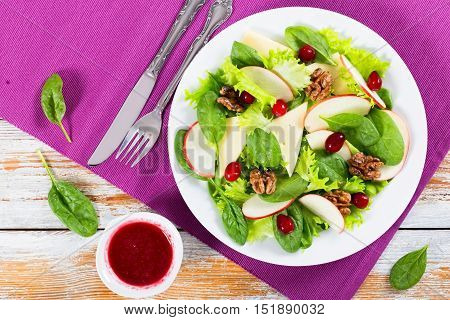salad of apple spinach cheese lettuce leaves Frise caramelized walnuts cranberry on white dish on table mat with berry dressing in gravy boat view from above