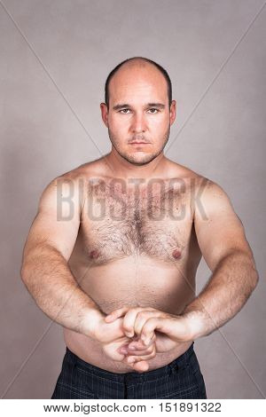 Portrait of serious shirtless man posing and showing his strong body.